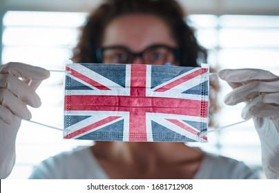 Pandemie des Coronavirus. Nahaufnahme von jungen Frauen mit chirurgischer Maske mit der britischen Flagge. Konzept von Coronavirus, COVID-19, Gesundheitsnotstand und Quarantäne