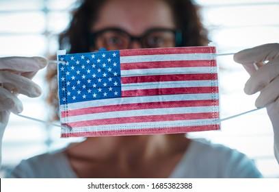 Pandemie des Coronavirus. Nahaufnahme einer jungen Frau mit chirurgischer Maske mit der US-Flagge darauf. Konzept von Coronavirus, COVID-19, Gesundheitsnotstand und Quarantäne