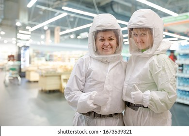 Pandemic virus concept. Two smiling virologist technician in PPE Personal Protective Equipment uniform gesturing OK in supermarket store while coronavirus COVID-19 pneumonia outbreak epidemic disease