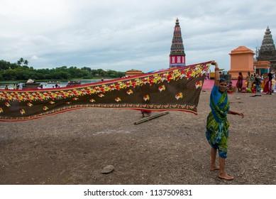 Pandharpur / India 16 July 2018 Indian Maharashtrian woman pilgrims drying their colorful sarees after taking holy bath near Pundalik Temple at Pandharpur Maharashtra India
