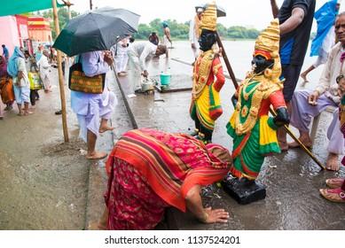 Pandharpur / India 16 July 2018 Hindu women pilgrims worshiping idol of Lord Vitthal and goddess Rukhmai on the banks of Chandrabhaga River in Pandharpur Maharashtra India
