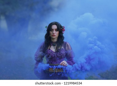 Pandora's box The treacherous brunette girl in a luxurious dress holds an open casket in her hands and stares intently into the camera with blue eyes. cool smoke in beautiful clouds fills the