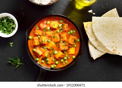 Paneer butter masala. Indian style cottage cheese curry in frying pan on black stone background. Top view, flat lay
