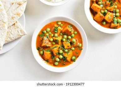 Paneer butter masala. Indian style cottage cheese curry in bowl over white stone background with free text space. Top view, flat lay
