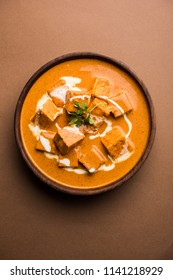 Paneer Butter Masala also known as Panir  makhani or makhanwala. served in a ceramic or terracotta bowl with fresh cream and coriander. Isolated over colourful moody background. selective focus