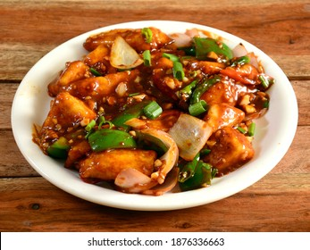 Paneer chilli is Indo Chinese cuisine dish, Paneer cubes tossed with tomatoes, onions, spring onions, chilli sauce. served over a rustic wooden background, selective focus