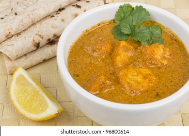Paneer Makhani or Shahi Paneer (Paneer Butter Masala) - Indian curd cheese curry served with chapatis and a wedge of lemon.