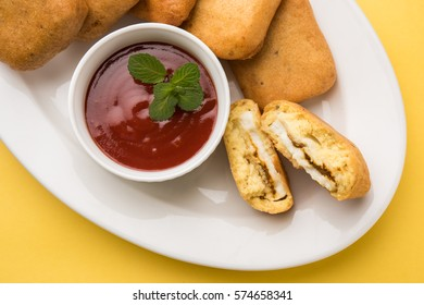 Paneer pakoras or Bhajji are gram flour (besan) batter coated spicy Cottage Cheese cubes. Served with tomato Ketchup in a plate over colourful / wooden background. Selective focus