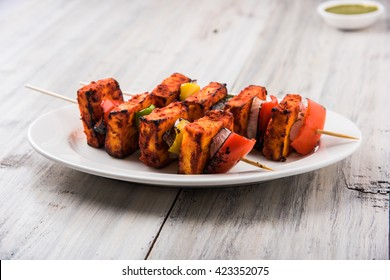 Paneer Tikka Kabab in red sauce - is an Indian dish made from chunks of cottage cheese marinated in spices & grilled in a tandoor. Served in a plate with salad & green mint chutney. Selective focus