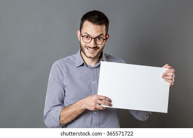 panel announcement - fun young man with eyeglasses and beard holding a copy space banner for teasing, gray background