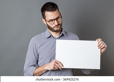 panel announcement - skeptical young man with beard and eyeglasses holding a blank banner for copy space text, gray background