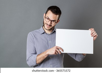 panel announcement - smiling young man with beard and eyeglasses holding a blank banner for copy space text, gray background