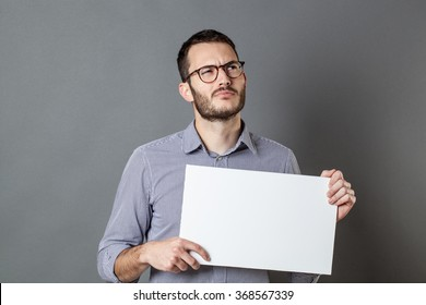 panel announcement - thinking young businessman with eyeglasses holding a blank banner with imagination and inspiration, gray background