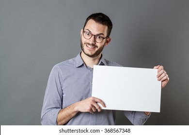 panel announcement - thrilled young businessman with beard and eyeglasses holding a blank banner for copy space text, gray background