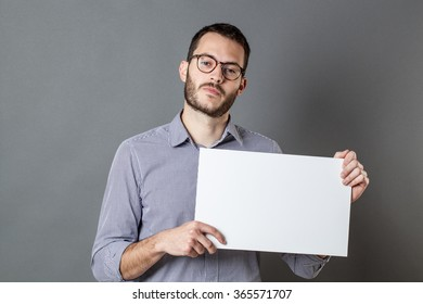 panel announcement - unhappy young man with beard and eyeglasses claiming for a strike on a blank banner for copy space text, gray background