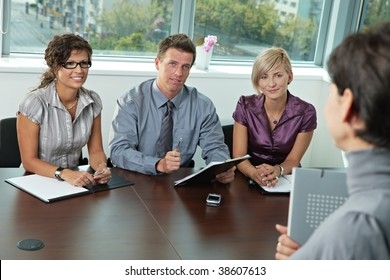 Panel of business people sitting at table in meeting room conducting job interview. Applicant holding folder.