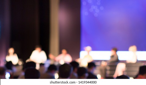 Panel speakers giving speech at blurred business seminar in auditorium. Background of presenters in hall meeting during lecture. Defocused businessmen in conference hall with bokeh.