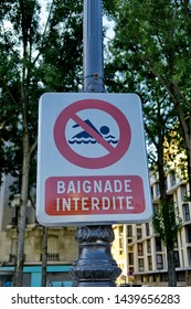 Panel with swimmer drawing crossed out in red. Text written in French: Swimming prohibited. French text: Baignade interdite.