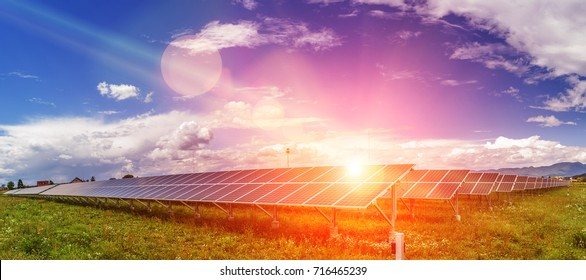 Panels of the solar energy plant under the blue sky with white clouds with sun flare hitting the surface - clean energy concept