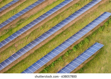 Panels in a solar farm, set in a uniform pattern within the rural landscape. Seen from the air. The industrialization of countryside. Essex, England.