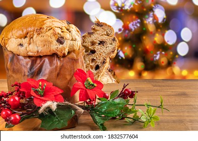 Panettone with chocolate, traditional Italian dessert cake for Christmas. Flashing lights and blurred decorations in the background.