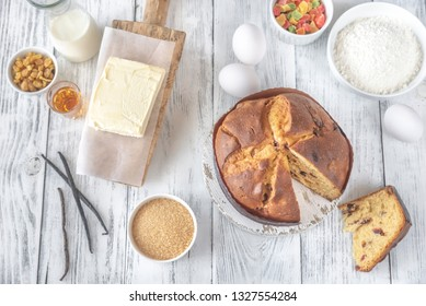 Panettone with ingredients on the white wooden table