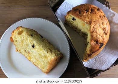 Panettone inside box on wooden table, slice of panettone on plate, top view