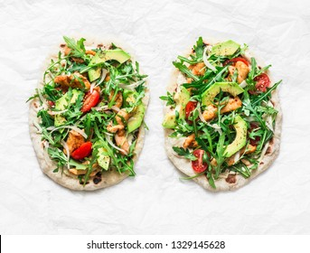 Pan-fried flatbread chicken, avocado, tomatoes, arugula pizza on a light background, top view