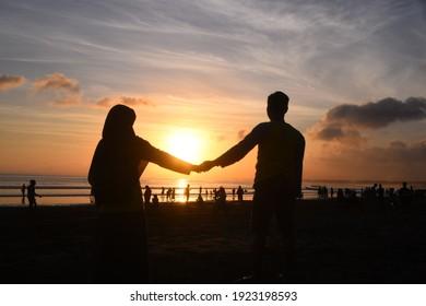 Pangandaran Indonesia, August 17, 2019; silhouette of tourists enjoying the sunset on Pangandaran Beach, West Java
