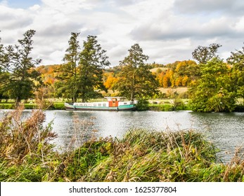 Pangbourne in Berkshire view of River Thames in October with single large boat.