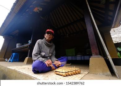 Panglipuran Tourism Village, Bangli, Bali - Indonesia, July 05, 2019. a man playing traditional music instrument in the bali traditional village of Penglipuran