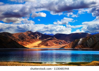 Pangong Tso (lake), Ladakh, Jammu & Kashmir, Northern India. Beautiful scenic view - colorful red and brown mountain range, bright blue water at the background of cloudy sky