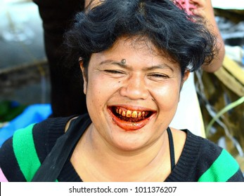 PANGURURAN, INDONESIA - APRIL 25, 2012: A young Indonesian Batak market woman with betel-stained red teeth/lips chews a betel quid (paan, chewing tobacco) and poses for the camera, on April 25, 2012.
