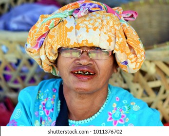PANGURURAN, INDONESIA - APRIL 25, 2012: A middle-aged Indonesian Batak market woman with betel-stained red teeth chews a betel quid (paan, chewing tobacco) and poses for the camera, on April 25, 2012.