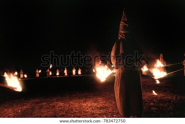 Panhandle, Florida, United States - circa 1995 - Ku Klux Klan KKK Night Ceremony, Members Wearing White Robes, Hoods and Carrying Burning Torches, Standing in a Circle