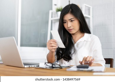 The panic Asian woman checking expensive electricity and house hold bills, reads documents attentively, prepares financial report, calculates on laptop computer. finance interior,domestic housework