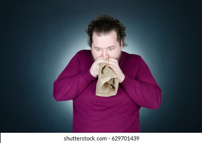 Panic attack. A man is holding a paper bag.