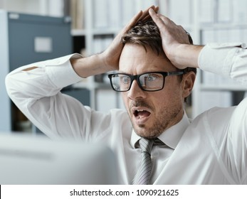 Panicking businessman with head in hands in his office, he is receiving shocking bad news on his computer