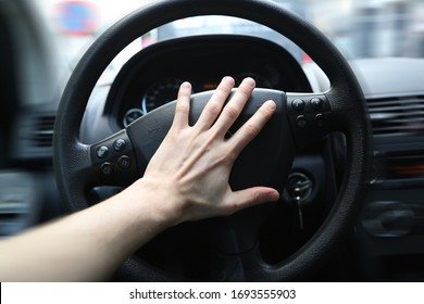 A panicking hand pushing the steering wheel of a car whilst driving. Honking the horn can be used to avoid an accident in a dangerous situation. The car is clearly driving fast, or is even speeding.