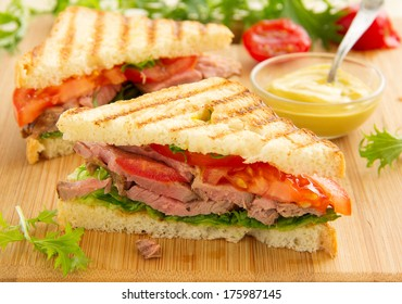 Panini closeup with roast beef and salad.