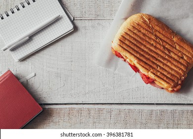 Panini with pen and notepad on office wooden table