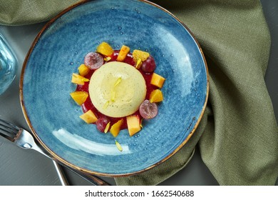 Panna Cotta - a delicious and beautiful dessert made of cream and vanilla with grapes and peach in a blue bowl on a wooden background. Top view, flat lay, copy space