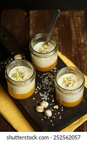 Panna cotta with mango, coconut and pistachios on a wooden cutting board