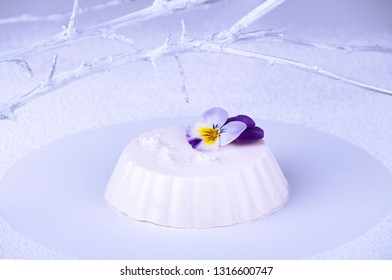 Panna cotta of white cocolate and wipped cream decorated with edible violet flower over on white background with white branch
