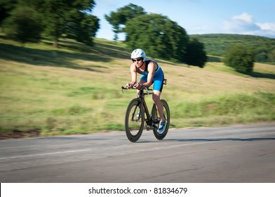 Panned shot of bicyclist in biking gear riding fast.