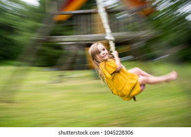 Panned Shot on young girl on rope swing