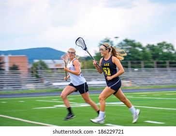 Panning blur featured as two female lacrosse players race down the field. High degree of motion conveyed. Some motion blur on athletes, particular in extremities, focus on face of closest player.