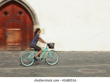 Panning image of a young woman riding her bicycle in a traditional city square in front of an old building with white wall.