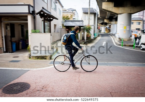 Panning shot of a man on bicycle in Kyoto, Japan