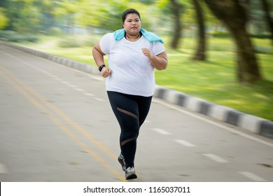 Panning shot of an Overweight woman jogging at park